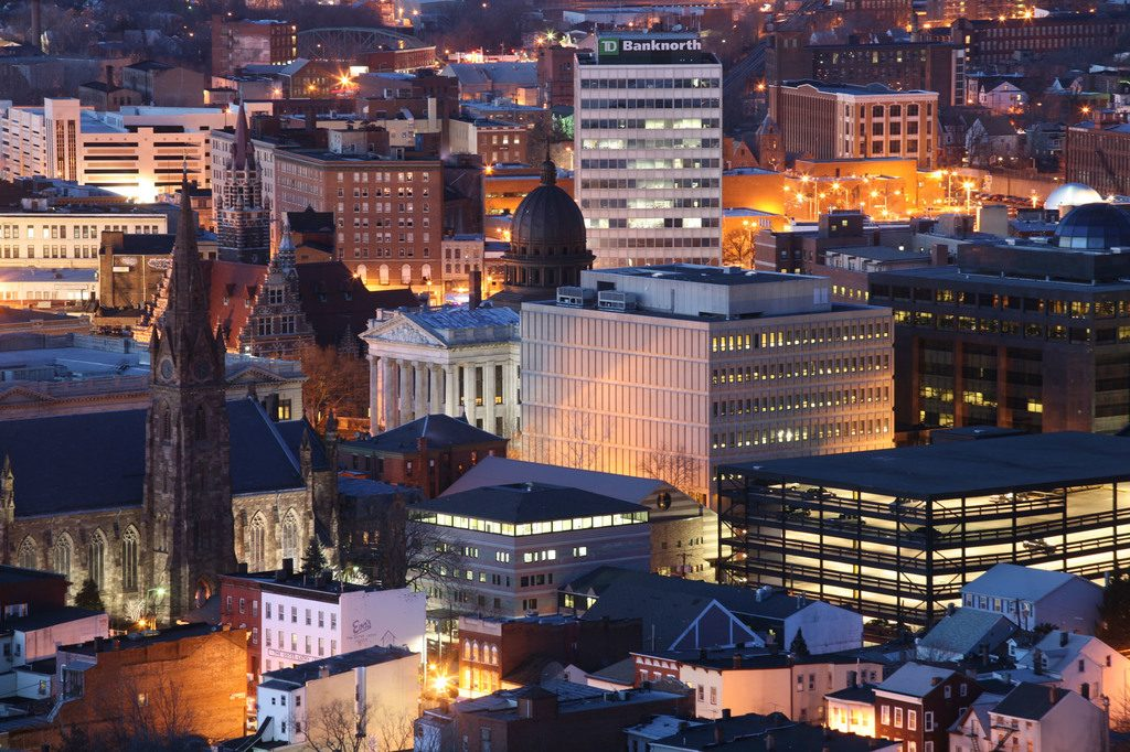 Picure of down town Paterson, NJ during the evening with all of the buildings lighting glowing in the eveneing dusk