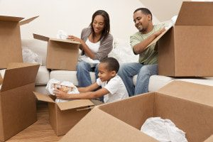 Picture of a mother, father, and sond packing their house items in boxes for moving in Paterson, NJ